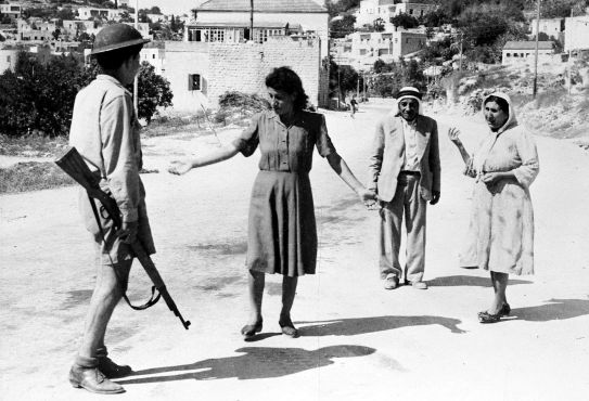 An Israeli soldier stopping some Arabs in a street in Nazareth July 1948 as they are traveling after the allotted curfew time. 1
